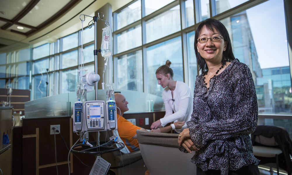 Vivian Lee, right, visits the Huntsman Cancer Institute's infusion center, part of the U Health Care system, where nurse Brandi Welker helps patient Jay Holt. (Photo by August Miller)