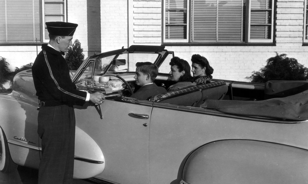 """J.W. """"Bill"""" Marriott, in the driver's seat, visits a Hot Shoppe during the 1950s. (All photos courtesy J.W. """"Bill"""" Marriott, Jr.)"""