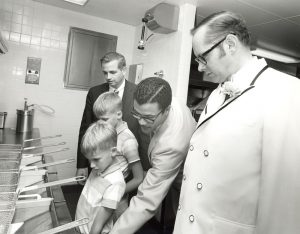 Bill Marriott, top left, works with his two young sons and a couple of employees in a company kitchen during the 1970s.