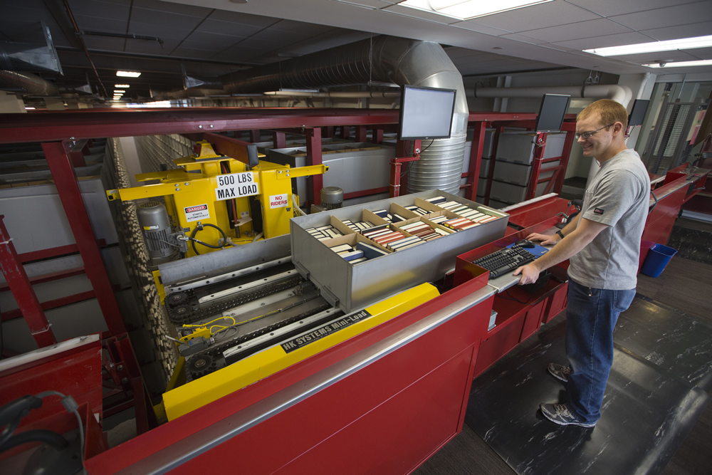 Library employee Chad Jones operates the automated retrieval machinery. (photo by August Miller)