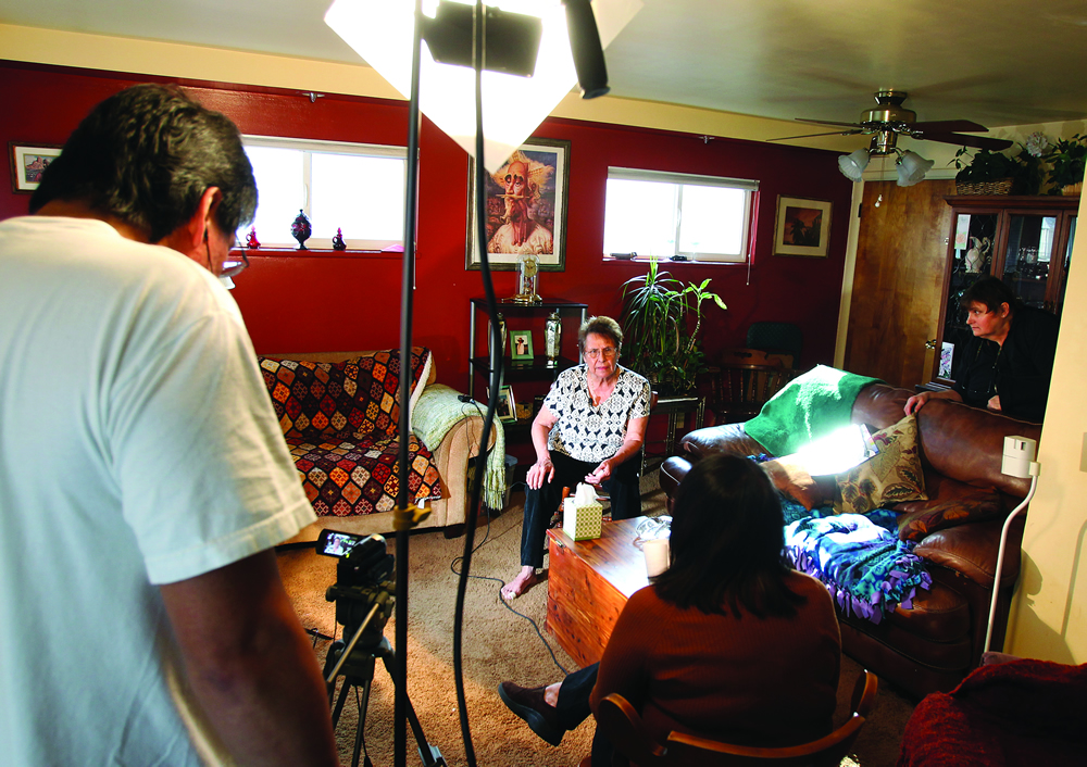 Beatriz Sanchez, center, answers questions while being interviewed and filmed at her home by Humanities in Focus students.