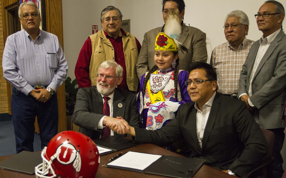 University President David Pershing, seated at left, shakes hands with Gordon Howell, chairman of the Ute Indian Tribe Business Committee.