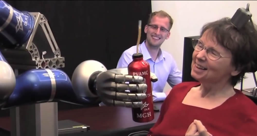 This paralyzed patient, at right, implanted with Richard Normann's Utah Electrode Array in a Brown University research study, was able to move a robotic arm with her thoughts. (Photo courtesy Braingate2.org)