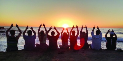 Members of the Student Alumni Board flash the U sign on a California beach after winning a CASE regional award.