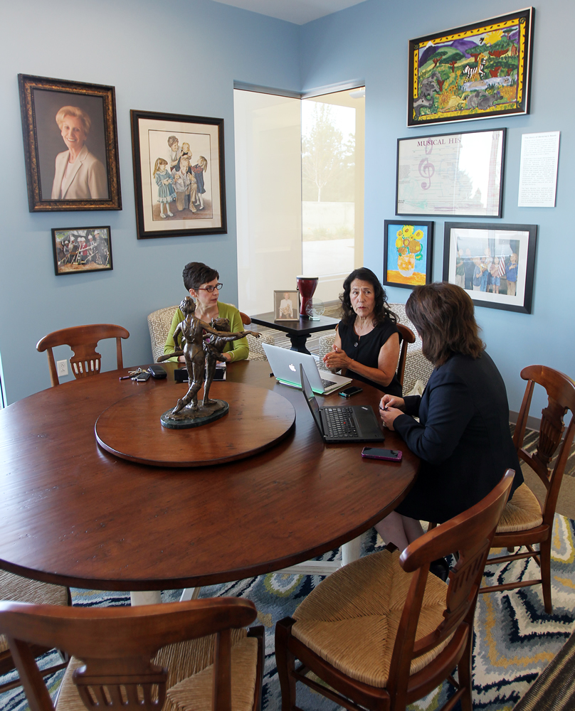 U education dean María Fránquiz, center, meets with Mary Burbank, left, assistant dean for teacher education, and associate dean Andrea Rorrer, at a replica of a table owned by Beverley Taylor Sorenson, whose portrait is on the wall. (Photo by Brian Nicholson)