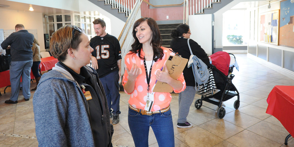 U intern Samantha Pehrson (holding the clipboard) learns on the job as she oversees a resource fair at Palmer Court.