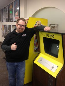 Roger Altizer, co-founder of the U Entertainment Arts & Engineering program, stands with an original Pong console (signed by Nolan Bushnell) that was donated to the program. (Photo courtesy Roger Altizer)