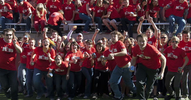 Members of The MUSS storm the field at Rice-Eccles Stadium to promote the University of Utah's Unrivaled Rivalry Food Drive.