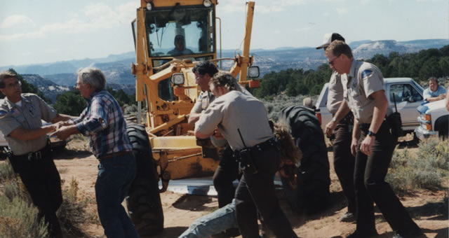Officers escort Ken Sleight, second from left, away during a protest near Moab in the early 1990s. (Photo courtesy The Canyon Country Zephyr, www.canyoncountryzephyr.com)