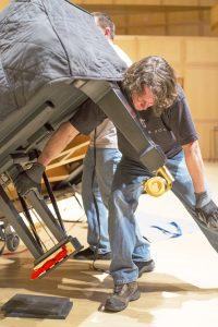 A worker places a newly delivered piano in Libby Gardner Concert Hall. (Photo courtesy U School of Music)