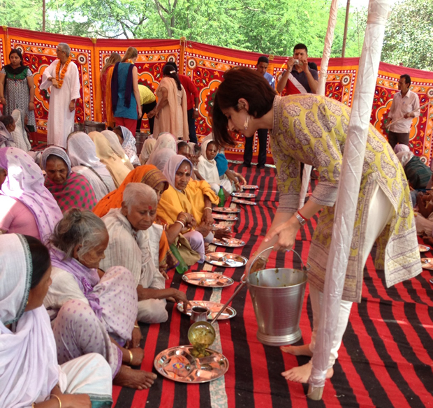 Sonal Singh Wadhwa, CEO of the nonprofit Maitri India, helps serve a meal to elderly widows. The group provides them with a meal once a day so they don't have to beg for food in the streets.