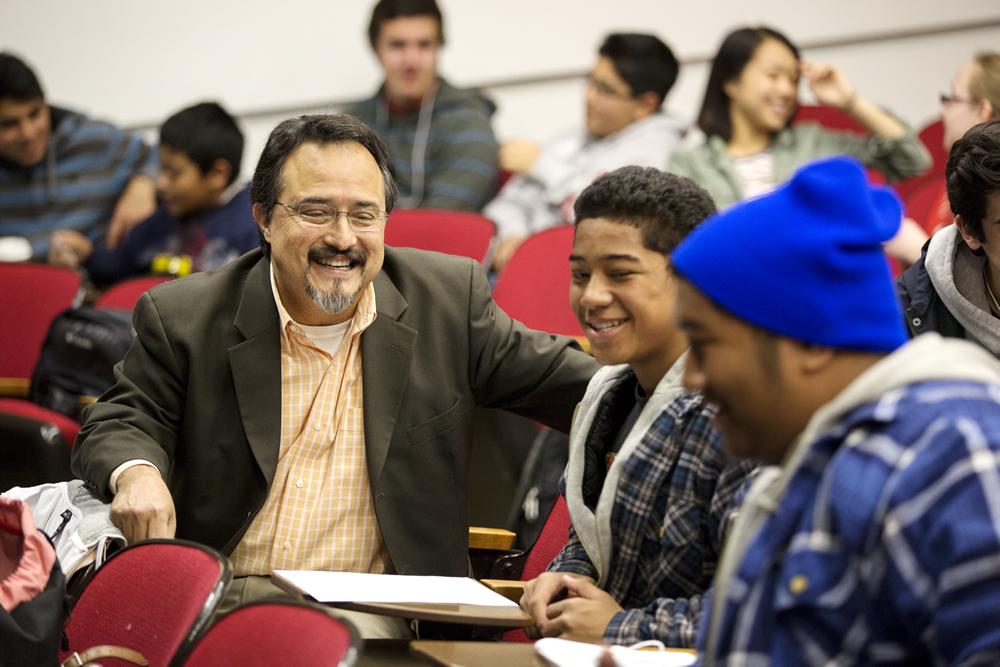 Octavio Villalpando, left, talks with a sixth grader and a University freshman Diversity Scholar.
