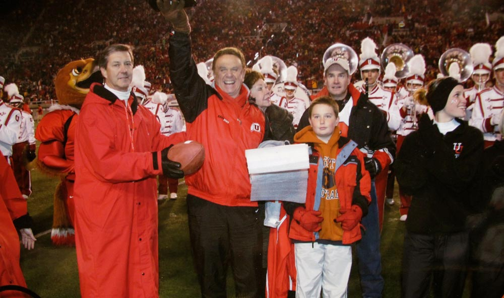 Bill Marcroft, second from left, celebrates with U Athletics Director Chris Hill, left, and others in November 2004, after Utah's football team defeated Brigham Young University, 52-21. (Photo courtesy Bill Marcroft)